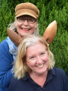 Portrait Louise Bastow and Michelle wake using gardenening trowels as bunny ears to illustrate contact the crafty gardeners for floral craft and garden workshops in bristol bath somerset and wiltshire