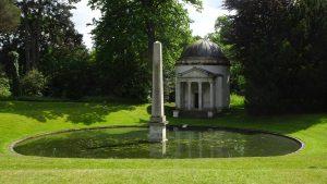 Image of a temple and obelisk at stourhead gardens to illustrate garden tours in somerset and wiltshire
