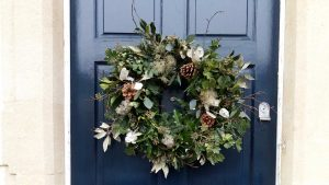 A christmas wreath hanging on the door of a house to illustrate christmas wreaths workshop